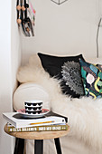Tasse und Bücher auf dem Hocker vor dem Sofa