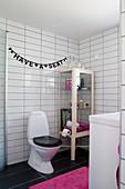 Girlande mit Spruch über der Toilette