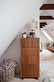 Chest of drawers with wood-grained fronts below sloping ceiling