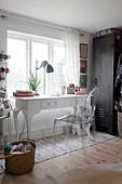 Designer chair at vintage-style desk below window