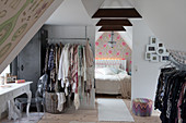 Clothes rails in attic room with open doorway leading into bedroom
