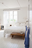 Blouse hung from open door leading into white bedroom