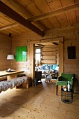Green retro armchair, wooden table and sheepskin rugs on wooden bench in dacha