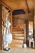 Staircase, tree-style coat rack and fur shoulder bags in dacha