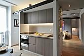 Reduzierte, beleuchtete Einbauküche in Appartement