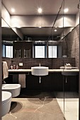 Designer bathroom with dark tiles and round white sink