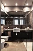 Designerbad mit dunklen Fliesen und rundem weißem Waschbecken