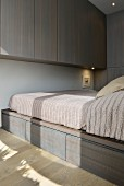 Fitted cupboards and bed on top of storage drawers in minimalist bedroom