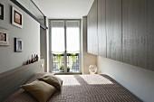 Maßgefertigte Hängeschränke und Doppelbett in reduziertem Schlafzimmer