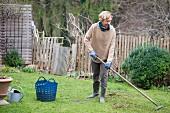 Woman raking thatch from lawn