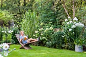 Woman reading on wooden lounger in well-tended garden