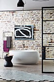 Modern freestanding tub in front of a wall with exposed brickwork