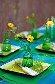 Festively set table in shades of blue and green outdoors