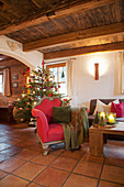 Christmas tree in rustic living room with red and green accents