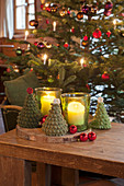 Crocheted fir trees and candle lanterns in front of Christmas tree