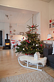 Sheepskin on sledge in front of Christmas tree in living room