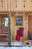 Schaukelstuhl mit roter Decke und Kissen hängt am Gartenhaus