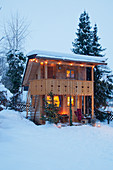 Alpine-style wooden cabin with illuminated interior in snowy garden