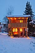 Beleuchtetes Holzhäuschen im Alpenstil im verschneiten Garten
