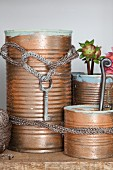 Recycled tin cans painted bronze and knitted cords