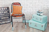 Mint-green suitcases, leather chair with knitted socks on legs and retro sign