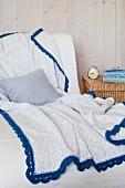 Grau-Weiß gemusterte Decke mit blauer Häkelborte