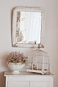Vintage birdcage an urn of flowers on white cabinet below mirror on wall