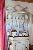 White crockery on wall-mounted shelves and kitchen utensils on old cabinet