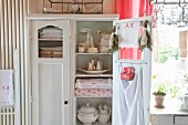 Table linen and kitchen utensils in old cupboard with open door