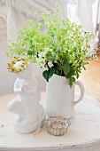 White jug of flowers, tealight holder and china ornament on table