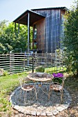 Vintage table and chairs on terrace in garden outside house with wooden façade