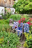 Crocheted blanket and cushions on wooden bench in idyllic cottage garden