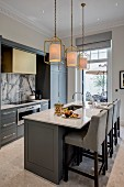 Island counter and upholstered bar stools in elegant kitchen