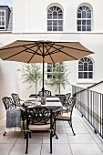 Metal table and chairs on balcony in front of façade with arched windows