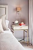 Bedside table on gilt frame below scone lamp