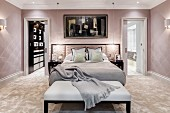 Glamorous bedroom in pastel shades with bench at foot of bed