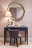 Upholstered chair at console table below round mirror