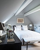 Double bed and bench below roof beams