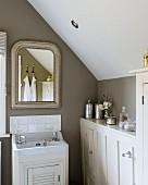 Bad mit Einbaumöbeln und Wandspiegel in Dachgeschoss