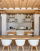 Dining table and modern shell chairs in Mediterranean kitchen