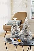 Kleine Weihnachtsbäume aus Zeitungspapier auf einem Tischchen