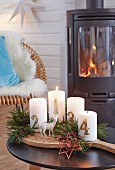 Advent candles with pine sprigs on a wooden board in front of a wood-burning kiln