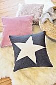 Kissen mit Stern auf einem Schaffell am Boden