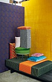 A pile of cushions and upholstery in front of two brightly coloured walls