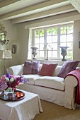 Scatter cushions on loose-covered sofa below lattice window in country-house interior