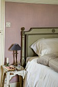 Shabby-chic wooden stool used as bedside table next to bed with wooden headboard