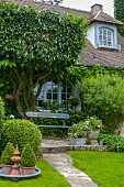 Vintage bench on terrace outside climber-covered country house
