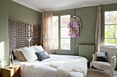 Sheepskin blanket on double bed with screen used as headboard in olive-green bedroom