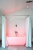 White bathtub with shower curtain bathed in pink light in renovated period building