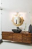 Black sink on elegant washstand below round mirror with ornate gilt frame